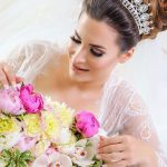 Beautiful bride looking at her bouquet of pink peonies, white orchids and snaps while wearing her dress and wedding crown