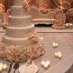 Five tier white wedding cake decorated with blush color flowers, placed in front of a round table with candles at a wedding
