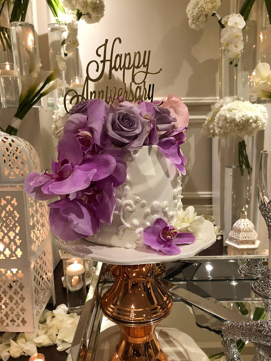 White Anniversary cake with purple orchids and roses on it placed on a table in front of white bouquet of flowers