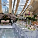 Wedding reception ballroom with upscale flowers, cherry blossom branches, bride and groom initials on the wall, gold drapes and tall centerpieces