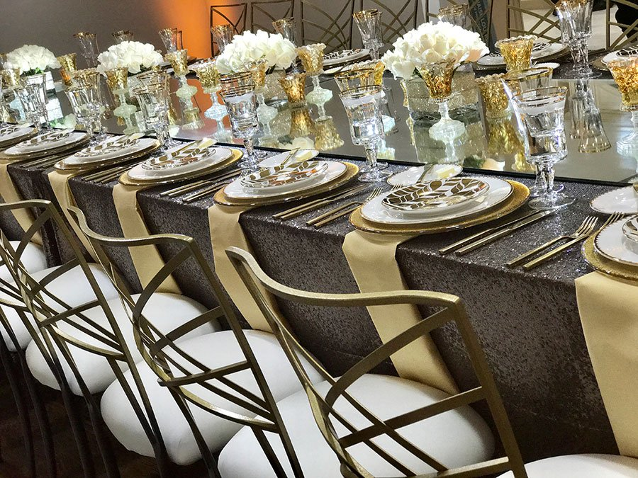 Gold, brown and white dinner table with white bouquet of roses and gold plate chargers